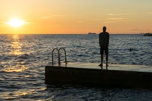 Man on the pier at sea sunset