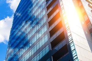 blue glass modern business center in summer with sun behind