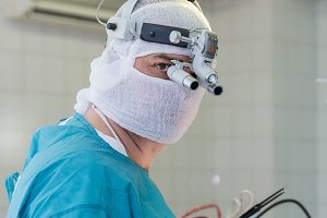 the surgeon with a magnifying glass