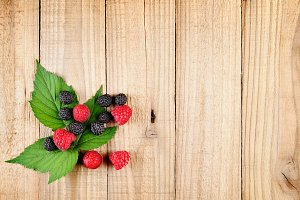Red and black raspberries on wood