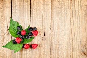 Red and black raspberries on wood