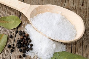 Salt in spoon and black pepper