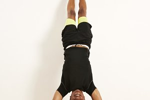 Smiling African American athlete doing handstand