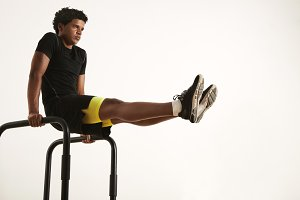 Young black man doing L-sits on short bars