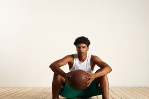Handsome young black basketball player sitting on the wooden floor