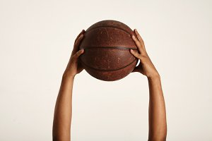 Closeup of a vintage basketball and two muscular dark-skinned hands