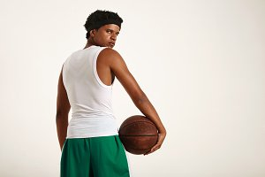 Back of a muscular black athlete holding  leather basketball