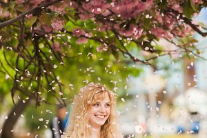 Smiling girl under sakura blossoms