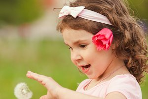 Curly girl with dandelion