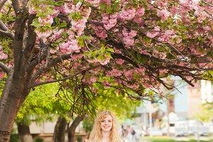 Smiling girl under sakura blossoms