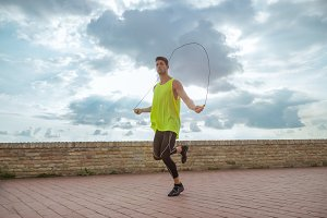 young man jumping rope sky sunny