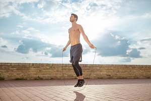 young man jumping rope shirtless
