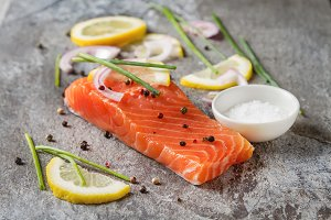 One piece of fresh salmon with lemon pepper and salt. Grey stone background