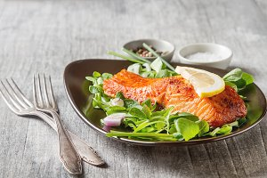 One piece of baked salmon grilled pepper lemon and salt on a brown plate with lettuce leaves. Grey wood background