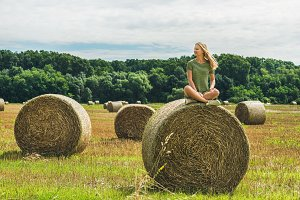 Young blond girl sitting on haystack