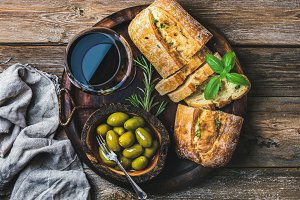 Red wine glass, olives and ciabatta