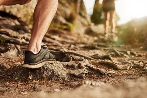 Man trail running on rocky terrain
