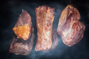 Pork meat hanging on hooks in smoke.