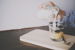 Hand pour milk to glass of espresso