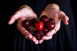sweet cherry in woman hand