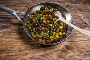 Skillet with fresh olives cooking