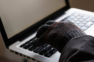 Man wearing gloves and using computer - fraud, hacker, theft, cyber crime concept