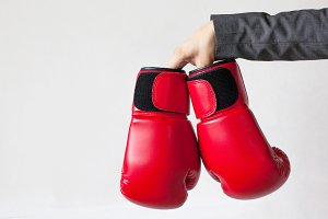 Businessman giving boxing gloves isolated on white background - indicates giving out the power, weapon to others