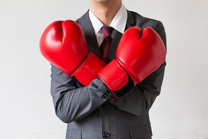 Businessman in boxing gloves guarding isolated on white background