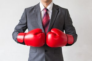 Businessman in boxing gloves isolated on white background