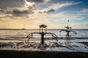 Traditional fishering boat in sunset sea with sky reflections in Bali, Indonesia