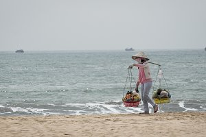 Women with conic hat walking on a beach near sea and carrying traditional baskets in Mui Ne, Vietnam