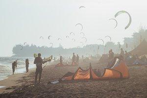 Kitesurfing scene at a very sunny day on a white sand beach near sea waves in kiting paradise - Mui Ne, Vietnam.