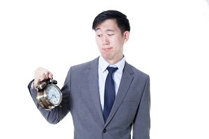 Young Asian businessman holding a clock in unpleasant face expression - business and time concept