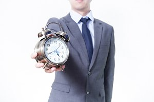 Man in Business Suit holding a clock - on time and business concept