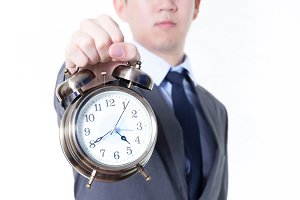 Businessman holding a clock in unpleasant face expression - business and time concept