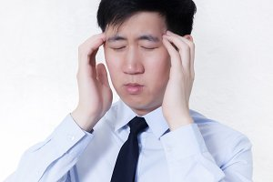 Young Asian businessman facing headache / migraine problems in white isolated