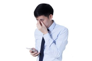 Young Asian businessman rubbing his tired eyes from long hours of works using smart phone