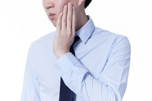 Young Asian man suffering from toothache / mouth problems
