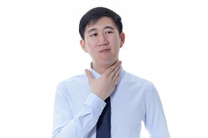 Young Asian man having sore throat / throat related diseases