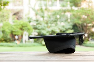 Graduation hat on vintage table with green nature background