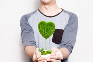 Young man holding a pot of tree in heart-shape in white isolated background - ecology and environment concept
