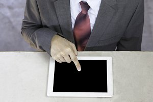 Executive businessman in suit touching and swiping in black blank empty tablet - ready to put any text or graphic onto screen