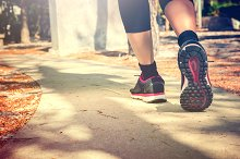 Running feet of young woman going by concrete trail in the park - in vintage tone