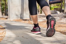 Running feet of young woman going by concrete trail in the park