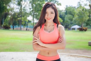 Young Asian fitness woman having her arms crossed with the park behind