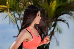 Young Asian fitness woman running in the park.