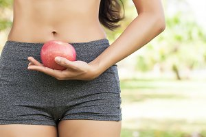 Healthy female holding apple at waist level outdoor in park