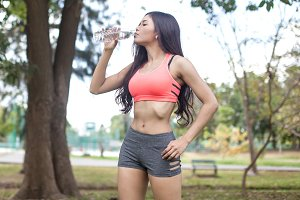 Asian Fitness Woman Drinking Water in the park