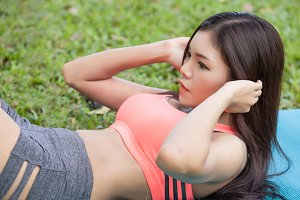 Exercise woman doing situps in outdoor workout training. Asian sport fitness woman focusing