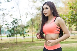 Young Asian fitness woman jogging and running in the park